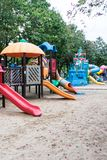 Blurred playgrounds at public park for kids. Blurred playgrounds and sand with trees at public park for kids Royalty Free Stock Image
