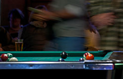Blurred Pool Table Action. A pool table with blurred people moving behind it royalty free stock photo