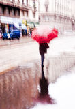 Blurred rainy day in the city. Intentionally motion blurred abstract image of a woman walking with a red umbrella under the rain Royalty Free Stock Photography