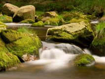 Blurred rapids of autumn mountain river, big mossy boulders obstruct water in foamy motion Stock Photography