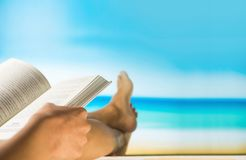 Blurred reading book and relax on beach table with sea view.  Stock Image