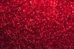 Blurred red background with circle sparkling lights. Shiny brilliant glittery bokeh of christmas garland. Dark wine backdrop royalty free stock images