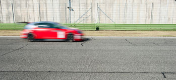 Blurred red car racing on track Royalty Free Stock Images