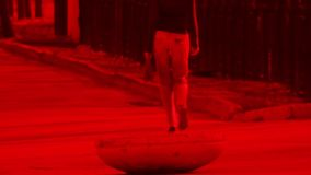 Blurred red colored shot. A young girl in jeans and a blouse wit.