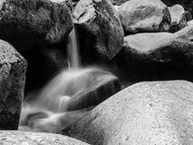 Blurred river stream detail. Of wild rocky mountain river. Silky effect. Motion rendition effect. Slow shutter speed effect. Long exposure effect. . Black and Stock Photography
