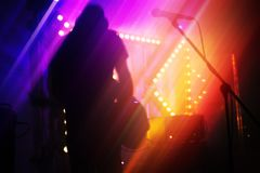 Blurred rock music abstract background. Bright colorful blurred rock music abstract background, bass guitar player on a stage Stock Image
