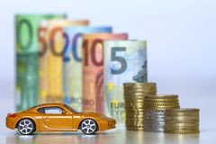 Blurred row of rolled hundred, fifty, twenty, ten and five new e. Uro banknotes and pile of coins with yellow toy expensive sport car. Symbol of financial Stock Image