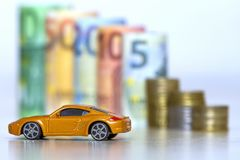 Blurred row of rolled hundred, fifty, twenty, ten and five new e. Uro banknotes and pile of coins with yellow toy expensive sport car. Symbol of financial Stock Images