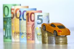 Blurred row of rolled hundred, fifty, twenty, ten and five new e. Uro banknotes and pile of coins with yellow toy expensive sport car. Symbol of financial Stock Photography