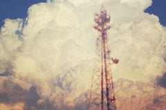 Blurred scene of electricity power post tower overlap on white cloud. Royalty Free Stock Photo