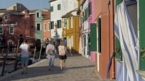 A blurred scenery of italian Burano with walking tourists. Colorful facades of small houses against the blue sky. Warm sunrays on a paved embankment. People in stock video