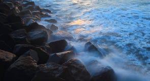 Blurred sea wave crashing over rocks. At Sunrise on The Cobb in Lyme Regis, Dorset Stock Image