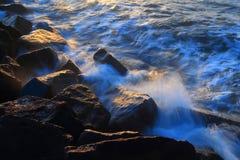 Blurred sea wave crashing over rocks. At Sunrise on The Cobb in Lyme Regis, Dorset Royalty Free Stock Images
