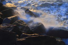 Blurred sea wave crashing over rocks. At Sunrise on The Cobb in Lyme Regis, Dorset Stock Photography