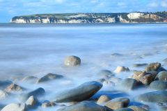 Blurred sea waves near town of Seaton. With Beer Head in background, Jurassic Coast Jurassic Coast  is designated a UNESCO World Heritage Site because of its Royalty Free Stock Photo