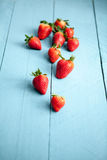 Blurred seasonal strawberries on blue wooden background Stock Photography