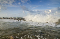 Blurred and selective focus image of wave hitting breakwater