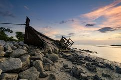 Silhouette image of abandon shipwrecked on rocky shoreline. dark cloud and soft on water Royalty Free Stock Photo