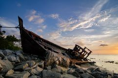 Silhouette image of abandon shipwrecked on rocky shoreline. dark cloud and soft on water Royalty Free Stock Photography