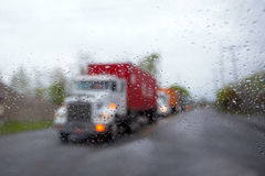 Blurred semi truck convoy in rain drops and headlight on road Royalty Free Stock Image