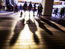 Blurred shoppers in shopping centre or commuters. Blurred shoppers or commuters casting shadows towards camera tinted for urban look Stock Photos