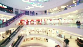 Blurred shopping mall center. Blurred shopping mall hall. Blurry walking people and escalators in shopping mall center stock video