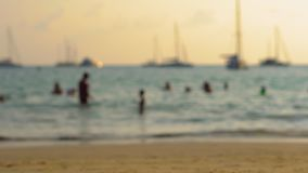 Blurred shot of a busy beach in tropics with silhouettes of people going by stock footage