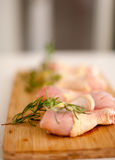 Blurred shot of chicken on a cutting board with fresh rosemary a Royalty Free Stock Photography