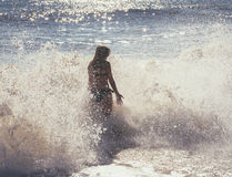 Blurred silhouette of a girl in a spray of sea foam and sunlight glare. A girl in a spray of sea foam on the beach summer day,blurred silhouetted,background Stock Images