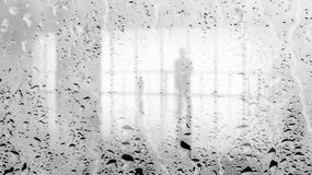 Blurred silhouette of man in the light hall through large wet glass wall. Black and white image.  stock photography