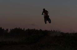 Blurred silhouette of motocross rider jumping on the mountain in sunset Royalty Free Stock Images