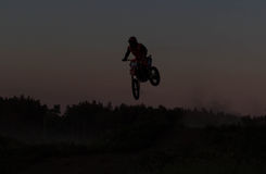 Blurred silhouette of motocross rider jumping on the mountain in sunset Royalty Free Stock Photography