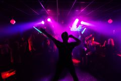 Blurred silhouette of the singer at a live concert at the club at the event against the crowd of people. In the audience stock illustration