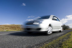 Blurred silver car on mountain road Stock Images