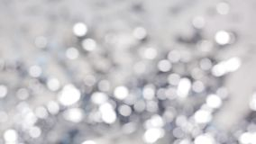 Blurred silver christmas lights bokeh. Holidays, luxury and background concept - blurred silver christmas lights bokeh stock video footage