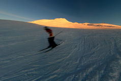 Blurred skier on mountainside. Blurred skier on snowy mountainside at sunset Stock Photo