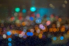Blurred skyline with bokeh effect seen behind a wet window with raindrops Royalty Free Stock Images