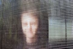 Blurred Smiling Young Face behind Dusty Fluted or Ribbed Glass, Clear Polycarbonate Corrugated Sheet. Online Anonymous, Anon. Communication, Data Security stock image