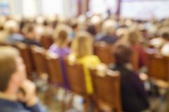 Blurred spectators sit on chairs. In rows in the theater and watch the performance Stock Photo