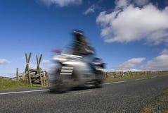 Blurred speeding motorbike on mountain road. Dartmoor, Devon, England Royalty Free Stock Image