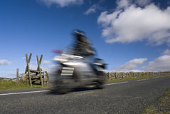 Blurred speeding motorbike on mountain road Royalty Free Stock Images