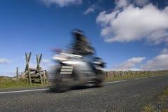 Blurred speeding motorbike on mountain road. Dartmoor, Devon, England Royalty Free Stock Images