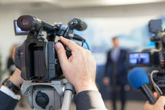 Blurred spokesman at press conference. Burred spokesperson at news conference Royalty Free Stock Photography