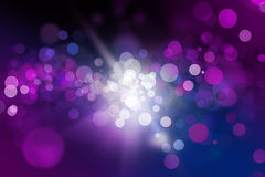Blurred spotlights background. Abstract defocused blurred spotlights in pinks and purples on blue background with white sparkle in the center Royalty Free Stock Images