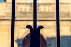 Blurred stone building behind a black wrought iron fence Royalty Free Stock Photography