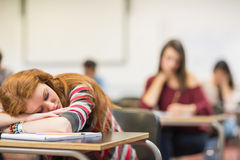 Blurred students in the classroom with one asleep girl Royalty Free Stock Image