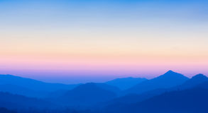 Blurred sunset over mountains. Stunning view of sunset over mountains - Defocused nature background Royalty Free Stock Image