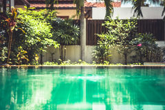 Blurred swimming pool background at backyard of tropical villa Stock Photos