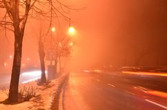 Tail lights on foggy night road. Blurred tail lights of passing cars in foggy atmosphere colored in red by street lamps. Long exposure photograph stock photography
