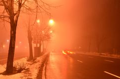 Tail lights on foggy night road. Blurred tail lights of passing cars in foggy reddish atmosphere colored by street lamps. Long exposure photograph. Speed royalty free stock photos